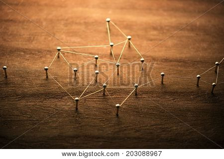 A small network developing in the data stream. Connecting people. Networking, social media, internet communication abstract concept image. Web of gold wires on rustic wood.