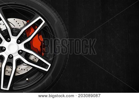 Alloy wheels of racing car with metal brake discs and red caliper on a black cement wall background with copy space your writing text on the right. Automotive parts concept.