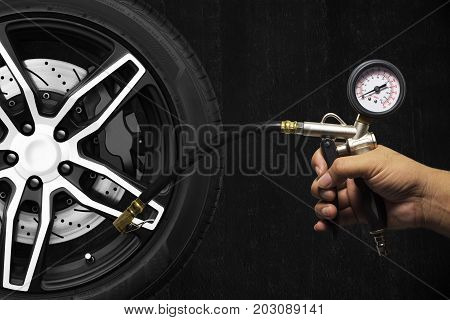 Hand holding an inflator gauge tools Alloy wheel of racing car and metal brake disc with black caliper Hand of mechanic man checking air pressure gauge of car tyre with black cement wall background.