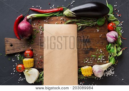 Cooking paper, parchment on wooden desk with vegetables and spices border on dark background, top view, copy space.