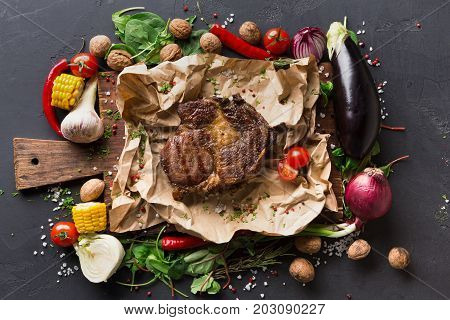 Rib eye steak on cooking paper or parchment on wooden desk with vegetables and spices border on dark background, top view.