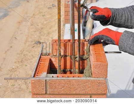 Bricklaying Closeup. Bricklayer hand holding a Putty Knife and Building a Brick Wall Column with Iron Bar Outdoor.