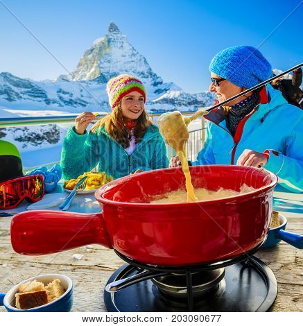 Swiss fondue cheese - skiers enjoying break for lunch, mountain view Matterhorn, Switzerland.
