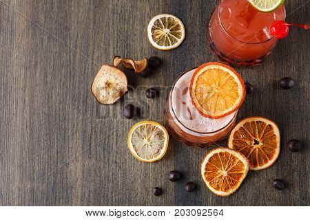 Cool alcohol cocktail at wooden background. Blood orange margarita with tequila on rustic table with citrons and chocolate snacks. Bar and restaurant backdrop with copy space for drinks menu, top view