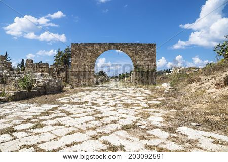 Byzantine road with triumph arch with blue sky and clouds in ruins of Tyre, Lebanon