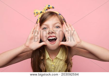 Portrait of little stylish girl on pink studio background holding hands near mouth shouting loud at camera.