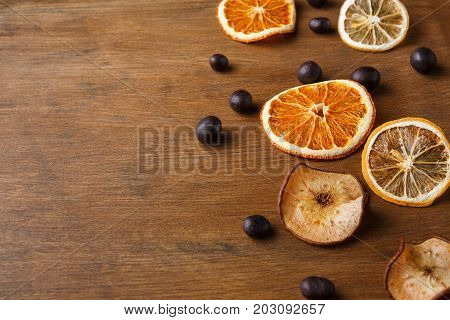 Dry orange, lemon, apple slices and small round chocolate sweets on wooden board. Candied citrus citrons with copy space. Cooking, confectionery or christmas background concept