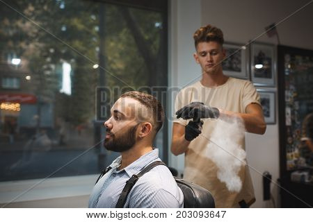 A thoughtful hairdresser spraying a hair fixation spray in a bottle. A successful hipster man sitting in a chair in a barbershop and a working barber on a blurred background. Copy space.