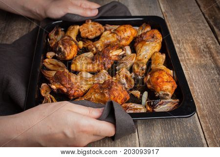 Female Hands Holding Hot Baking Sheet From Oven Baked Chicken Legs With Shallots And Garlic. A Woman