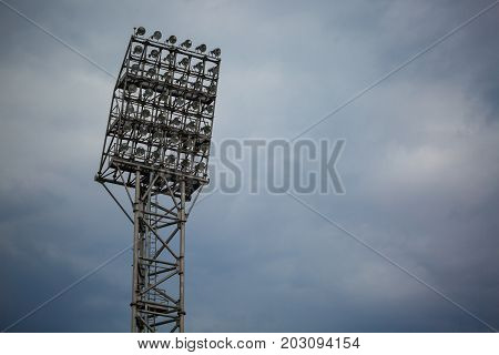 A tall, electric spot-light flash tower on a dark blue sky background. A professional Stadium illumination device. A modern electric lighting equipment for the outdoors. Copy space.