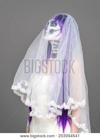 Portrait of woman looks upwards with terrifying halloween skeleton makeup and purple wig bridal veil wedding dress over gray background. Black wedding