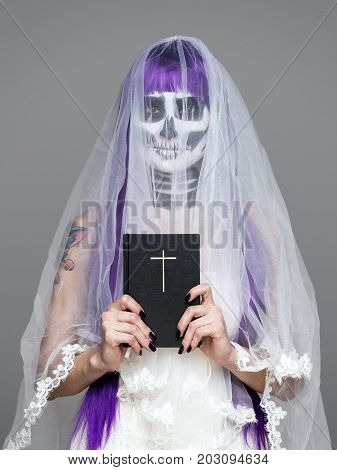 Portrait of woman looks at the camera with terrifying halloween skeleton makeup and purple wig bridal veil wedding dress holds the Holy Bible over gray background. Black wedding