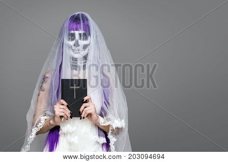 Portrait of woman looks at the camera with terrifying halloween skeleton makeup and purple wig bridal veil wedding dress holds the Holy Bible over gray background. Black wedding. Copy space