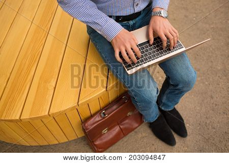Close-up picture of a corporate man typing on a new, modern, wireless laptop sitting on a blurred urban background. Top view of a young programmer with a pc. Wireless electronics technology concept.