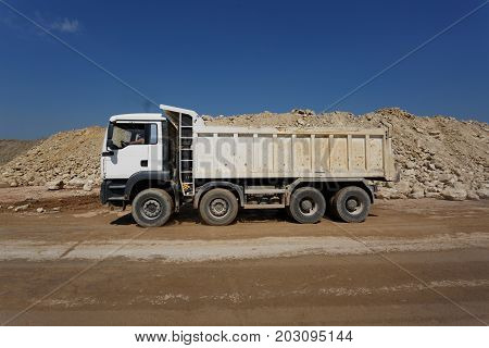 A white dump truck, a lorry with stones in a sand quarry, heaps of sand, a motor vehicle designed to transport cargo on a natural background.