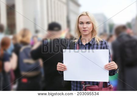 Concept of sexual minority. Woman holding blank poster during gay parade outdoors