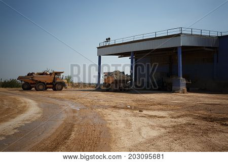 Tipper or dumper trucks, dump trucks full of stones in a sand quarry, transporting of sand, gravel, demolition waste on a natural background.