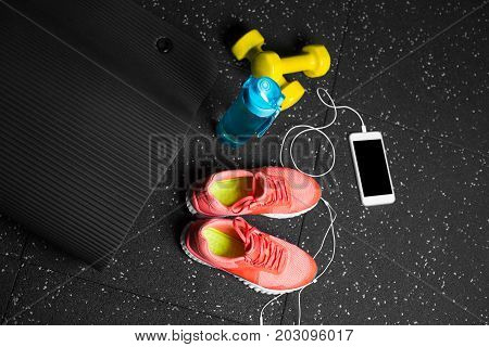 Bright yellow dumbbells, white headphones with a mobile phone, a blue bottle of water, vivid crimson women sneakers on a dark gray background.