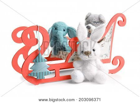 Sledge with cute toys on white background. Concept of baby's first Christmas