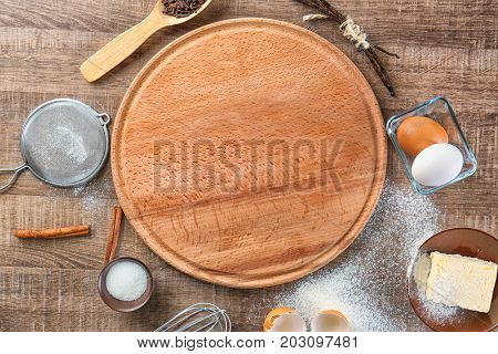 Composition with board and some products for cooking vanilla cake on wooden background
