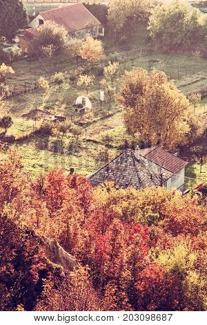 Close up photo of rural scene. Seasonal natural theme. Vibrant colors. House and gardens. Living in symbiosis. Red photo filter.