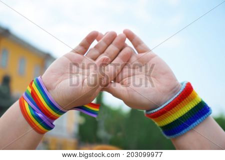 Concept of sexual minority. Female hands with rainbow LGBT symbols outdoors
