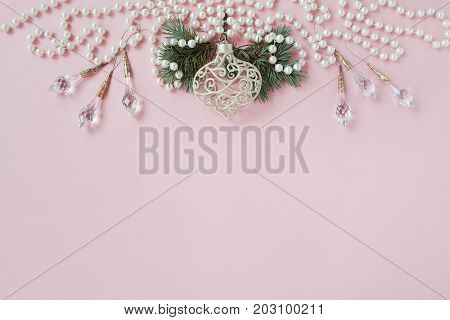 Christmas card pink tracery background with decorations pearl and blue spruce