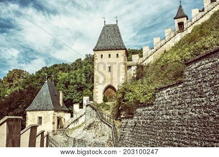 Gothic castle Karlstejn in Czech republic. Ancient architecture. Travel destination. Walls and turrets. Old photo filter.