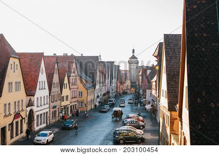 View from a high point to a beautiful street with traditional German houses in Rothenburg ob der Tauber in Germany. Ahead of the city tower. Sightseeing of the city.
