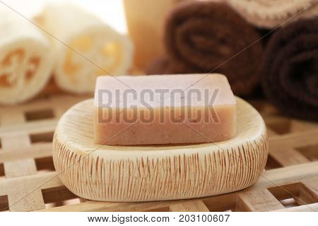 Aromatic soap and bath accessories on wicker table