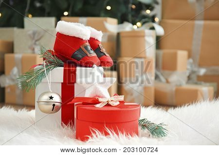 Cute booties for baby and gift boxes on furry carpet in decorated room for Christmas