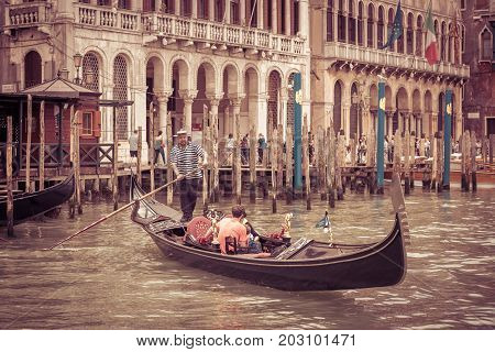 Venice, Italy - May 21, 2017: The gondola with tourists floats along the Grand Canal. Gondola is the most attractive tourist transport in Venice.