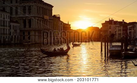 Grand Canal with gondolas at sunset in Venice, Italy. Grand Canal is one of the major water-traffic corridors and tourist attraction in Venice. 16:9 widescreen.