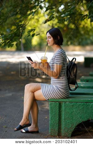A lovely, tender woman sitting on a bench in a park and texting a phone on a blurred background. Modern office worker holding a smart phone and drinking a green smoothie. Copy space.