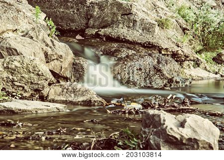 Water stream. Long time photo exposure. Detailed natural photo. Brook scene. Retro photo filter.