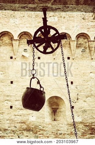 Metal bucket on a pulley hanging in the courtyard of the historic palace Siena Tuscany Italy. Yellow photo filter.