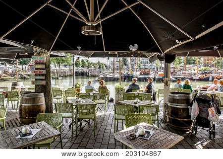 ROTTERDAM, NETHERLANDS - August 05, 2017: Outdoor cafe with people on the Oude haven in Rotterdam old city centre