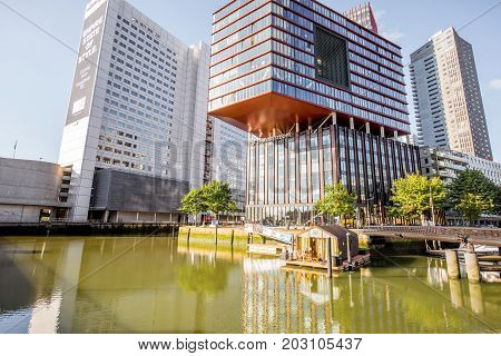 ROTTERDAM, NETHERLANDS - August 06, 2017: View on the Wijn port with Red Apple building and house on the water in Rotterdam