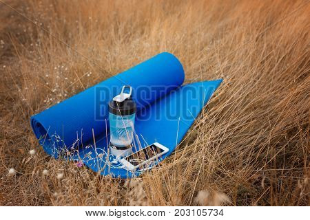 Close-up of a saturated blue sports mat for stretching, a bottle of water and smartphone on a yellow grass background. A composition of sports items in the field. Training on the fresh air concept.