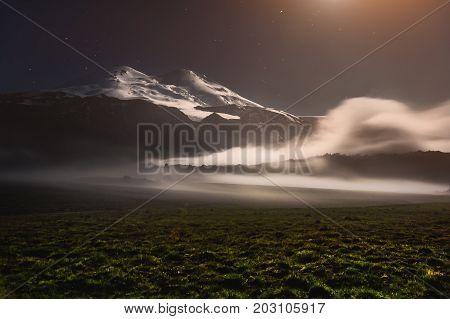 Night photo. Long exposure. Creeping cloud in the surroundings of the sleeping volcano Elbrus in the Caucasus at night in the light of the moon