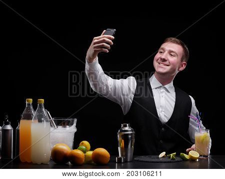 A bar counter with oranges, slices of lime, cocktails, lemon, a bartender takes a selfie on a black background. Party, night club, cafe, entertainment concept.