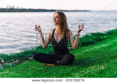 Young Girl Doing Yoga In The Park On Grass