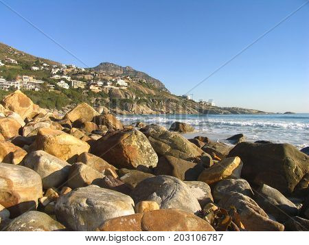 VIEW FROM LLUNDUDNO, CAPE TOWN, SOUTH AFRICA, WITH HUGE BOULDERS IN THE FORE GROUND AND A MOUNTAIN IN THE BACK GROUND 01cc