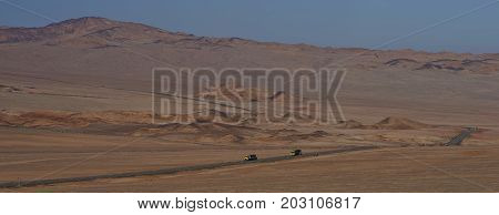 Atacama Desert, Chile - August 18, 2017: Vehicles on the Pan American Highway (Ruta 5) running through the harsh and arid landscape of the Atacama in northern Chile.