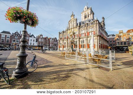 DELFT, NETHERLANDS - August 07, 2017: View on the Town hall and beautiful buildings on the central square during the sunny morning in Delft city, Netherland