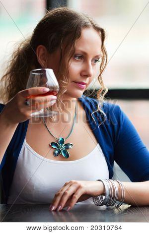 Beautiful young woman drinking cognac.