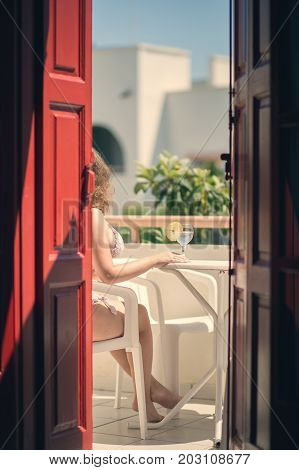 Female in a swimsuit sits on the balcony of an old Greek building with lemon water in a glass. Female legs on the balcony