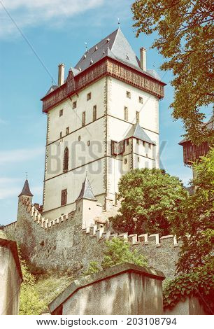 Karlstejn is a large gothic castle founded 1348 by Charles IV in Czech republic. Ancient architecture. Travel destination. Yellow photo filter.