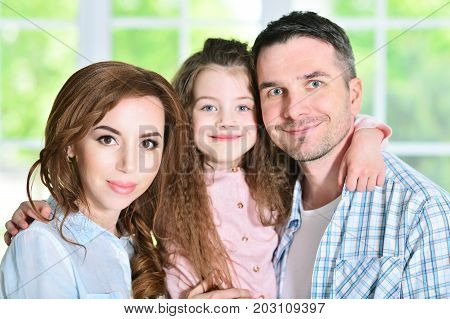 Close up portrait of cute little girl hugging her parents