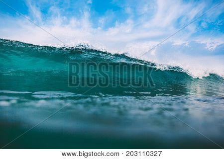 Shorebreak ocean wave in daylight. Sea water surface for surfing sport. Blue sky and waves